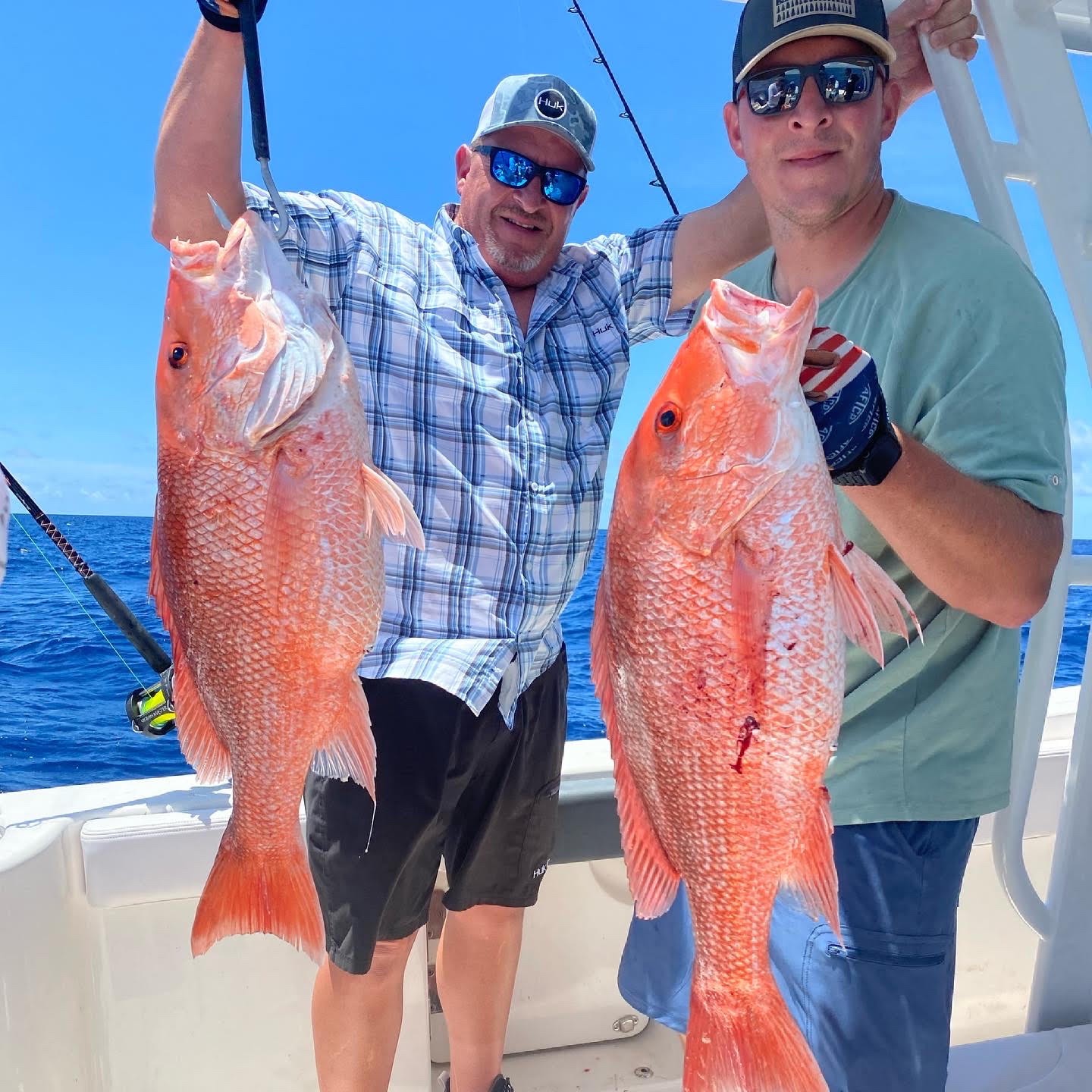 holding their newly caught red snapper
